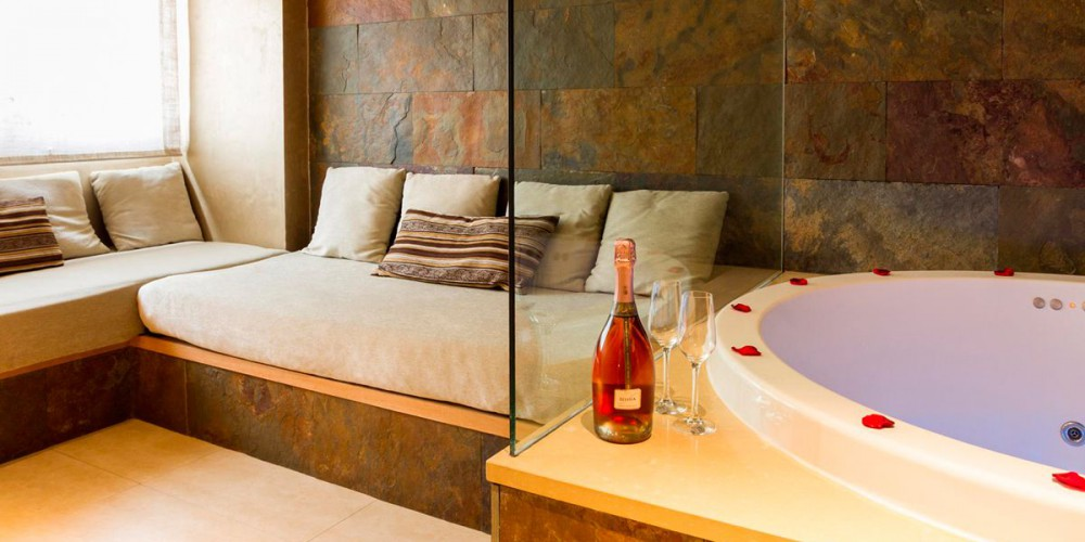 The Romantic Suite with jacuzzi has two areas separated by a bathroom-dressing room. In the living area there is an L-shaped sofa, TV and a large 1.60-metre Jacuzzi with chromotherapy.
